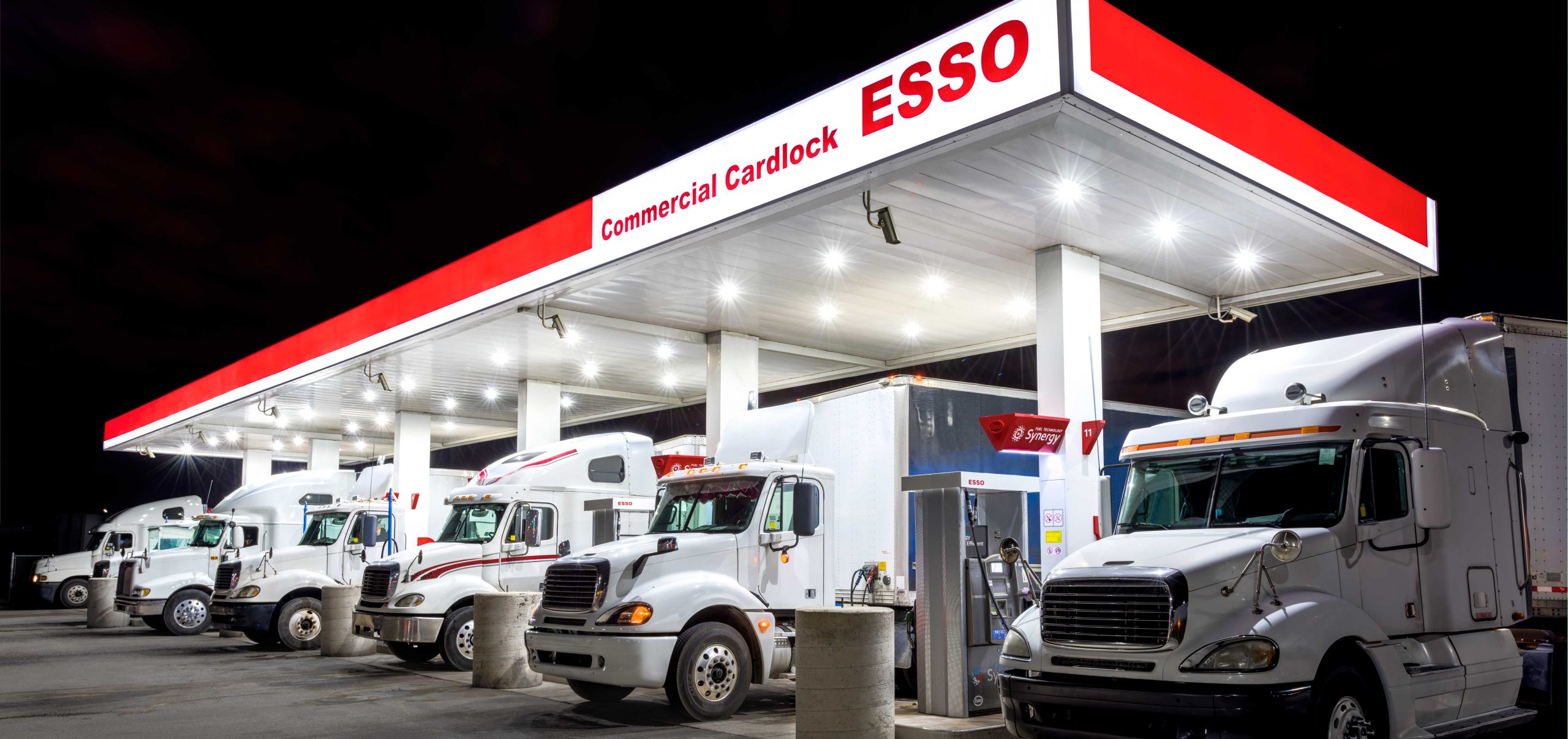 Photo of transport trucks parked under Esso cardlock canopy at night
