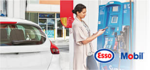 Photo of woman at gas station fuel dispenser, with Esso and Mobil logos